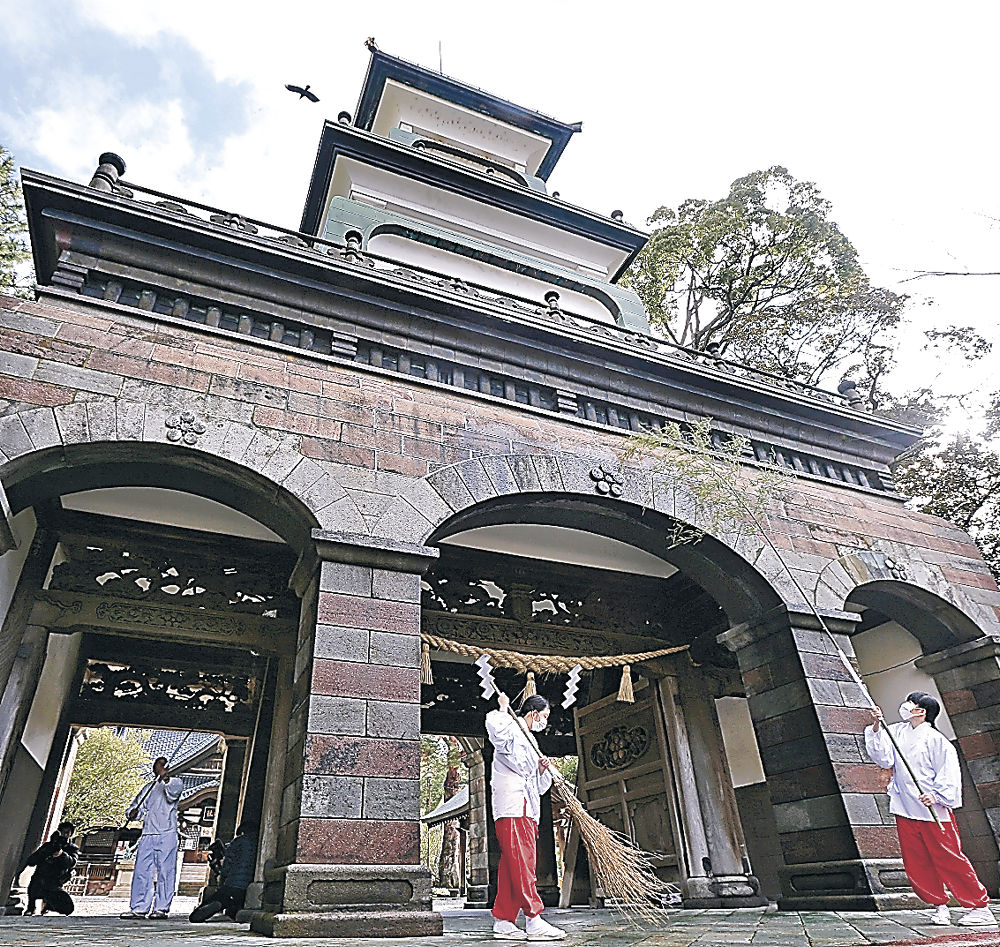 神門の汚れを落とす神職と巫女=尾山神社