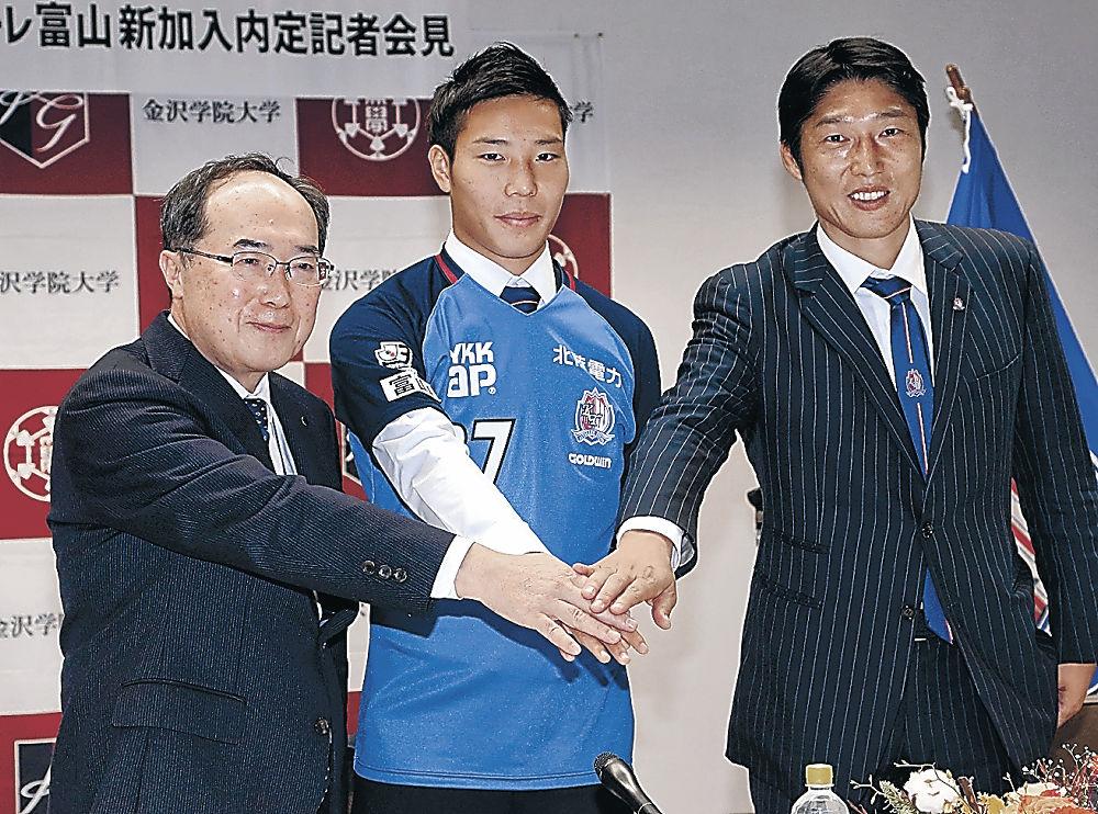 会見でユニホームを着た大谷選手(中央)と秋山学長(左)、黒部強化部長=金沢学院大