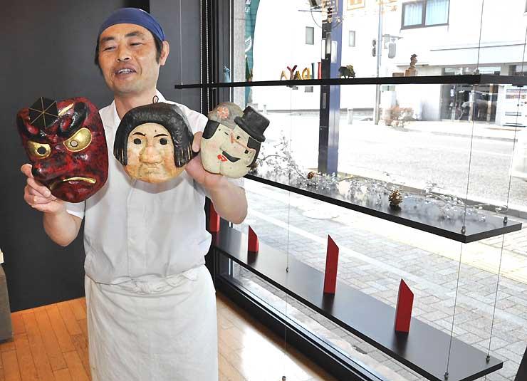 貸し出される棚(右)に飾る予定のお面を手にする相沢さん