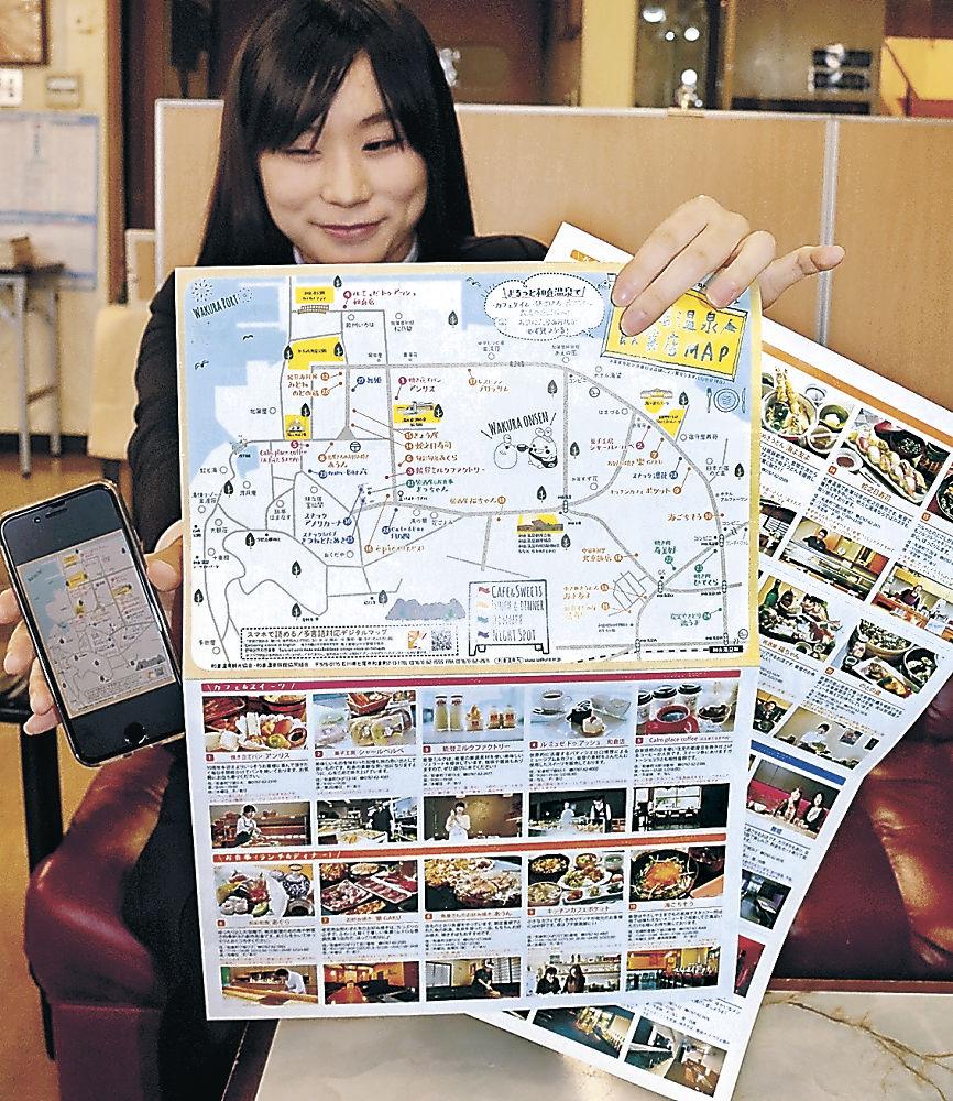 マップを手にする職員=七尾市の和倉温泉観光会館
