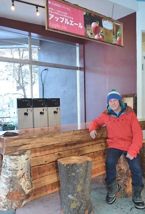 新たに設けたバーカウンターに座る猪狩さん。テーブルやいすは地元産の木材を使った