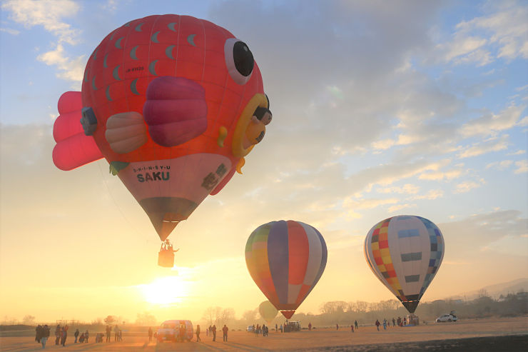 「サンタ」を乗せて飛び立つ熱気球=22日午前7時24分、佐久市