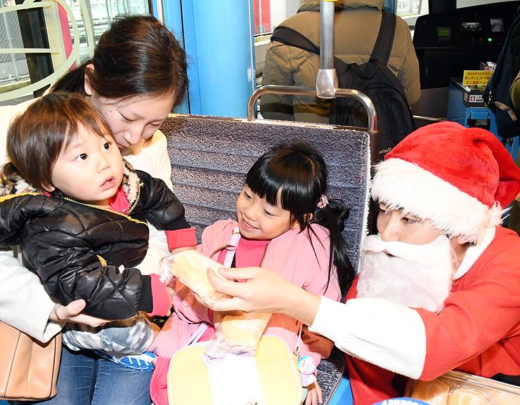 サンタクロース姿の社員(右)からプレゼントを受け取る子ども