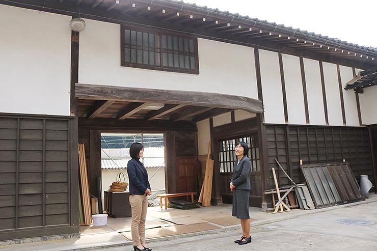 カフェに生まれ変わる門を前に、オープンに向けてスタッフと話し合う服部さん(右)=小矢部市安楽寺