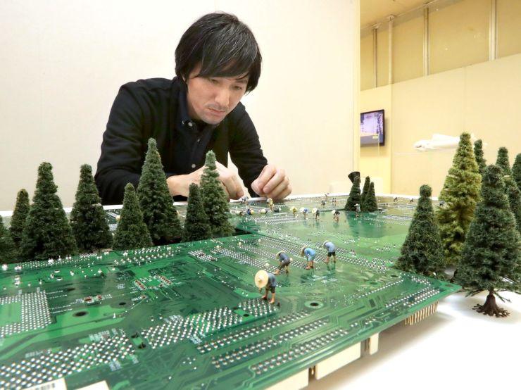 パソコンの基板を新潟の田んぼに見立てた作品を制作する田中達也さん=26日、新潟市中央区