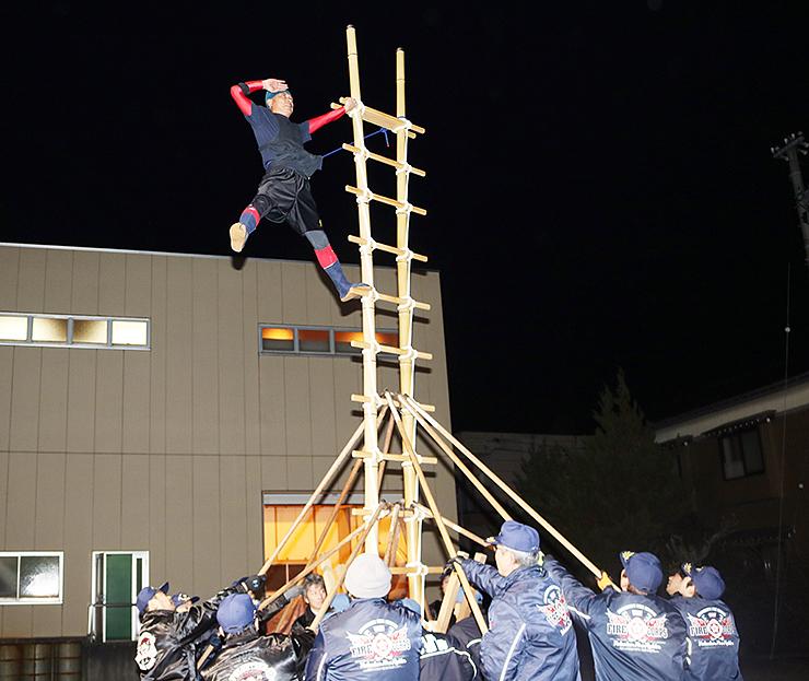 本番に向け、はしごの上で技を練習するメンバー