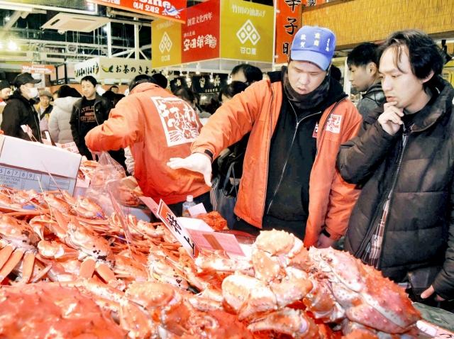 店員と交渉しながら品定めする買い物客=12月29日、福井県敦賀市の日本海さかな街