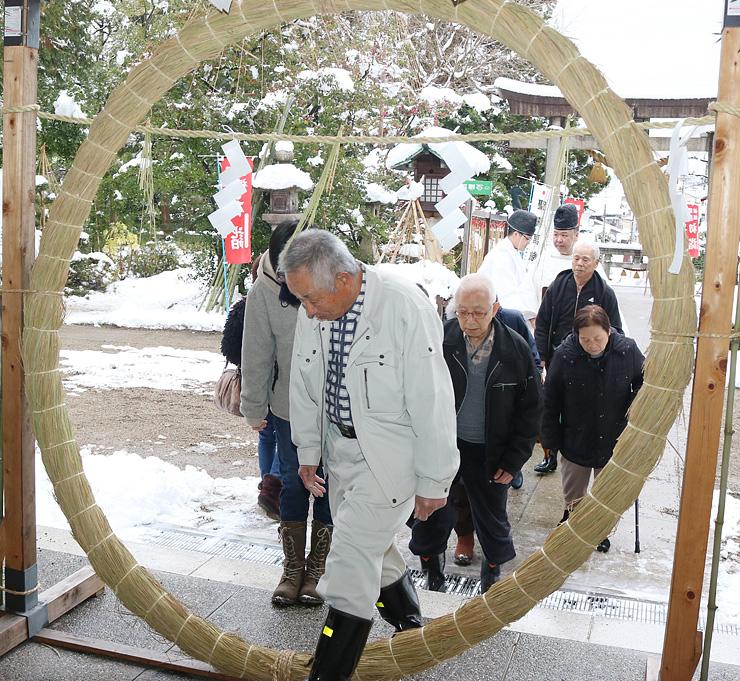茅の輪をくぐる参拝者=伏木神社