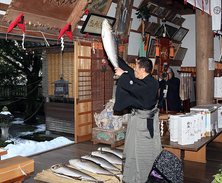 ブリを掲げ、地区名を読み上げる氏子の代表=下村加茂神社