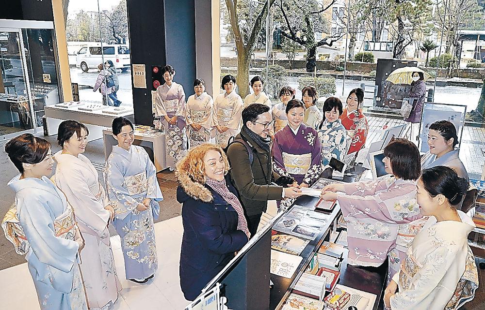 加賀友禅の着物姿で接客する女性会員=金沢能楽美術館