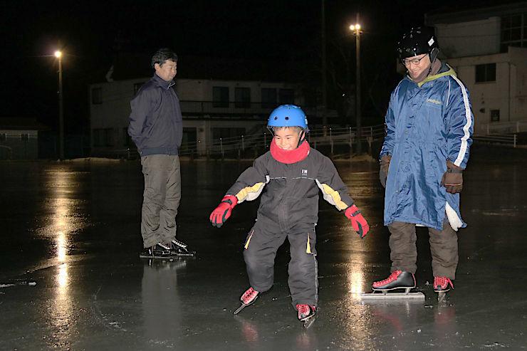 茅野市金沢小学校の校庭リンクでスケートを楽しむ親子(右の2人)=5日午後7時半