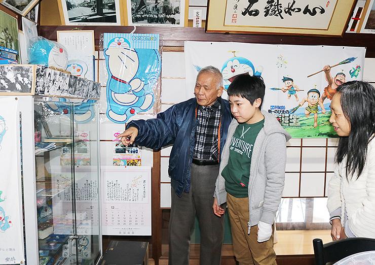 来館者に館内の説明をする石黒館長(左)