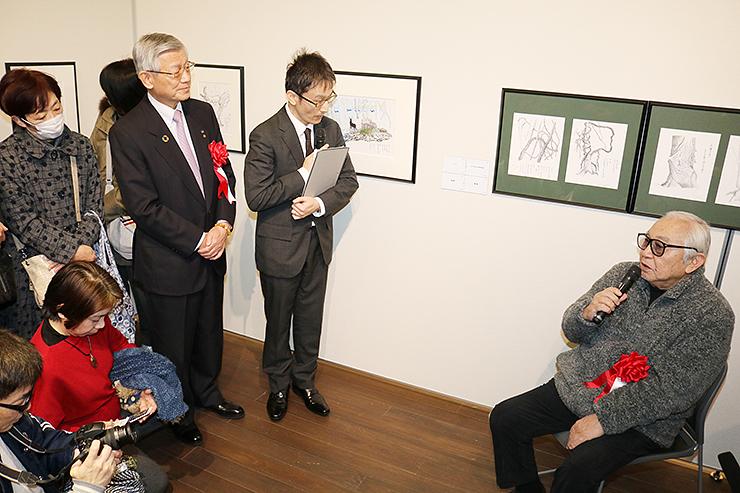 作品の前で点描画への思いを語る倉本さん(右)=高志の国文学館