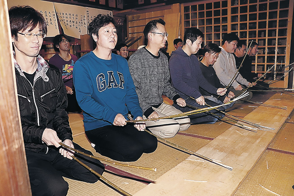 御宝木を激しくたたき付ける出席者=輪島市河井町の重蔵神社