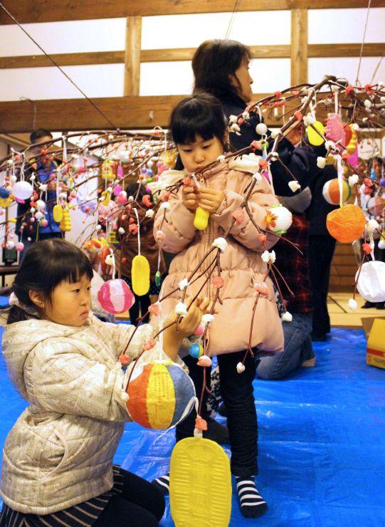 小正月行事の繭玉飾りを楽しむ子どもたち=6日、出雲崎町尼瀬