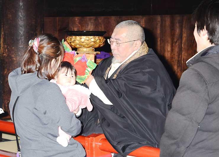 僧侶から御印文を頭に当ててもらう子ども