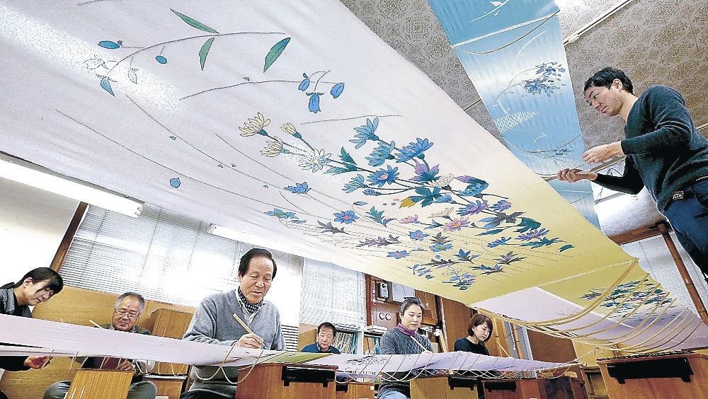 加賀友禅の彩色作業に励む職人=本多町3丁目の毎田染画工芸