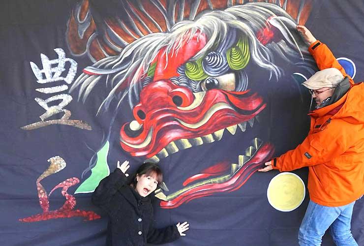 獅子舞の絵の前でポーズを取る吉沢さん(左)と前田さん