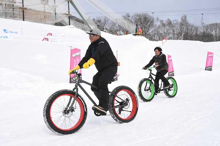 雪上を走る専用の自転車に乗る体験者