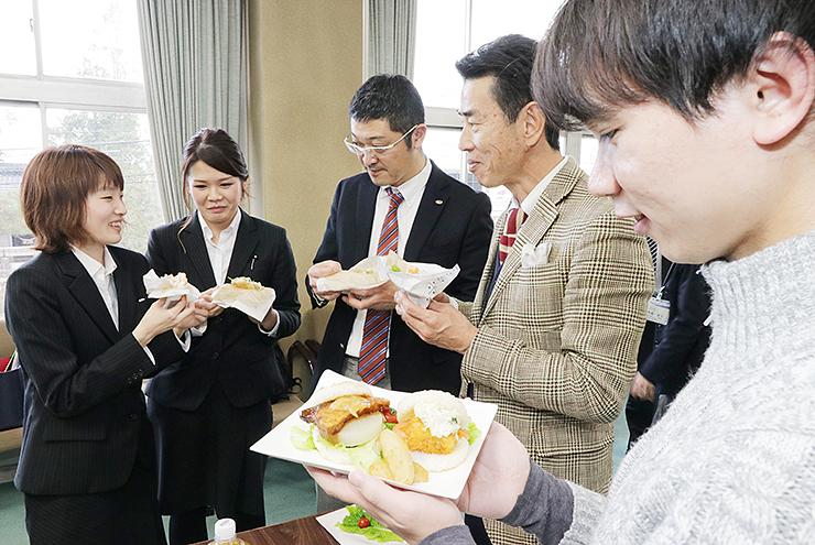 米騒動バーガーを試食し、笑顔を見せる参加者=魚津市役所