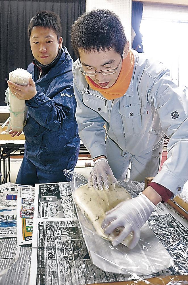 五角柱の型に餅を流して固める青年部員=白山市笠間公民館