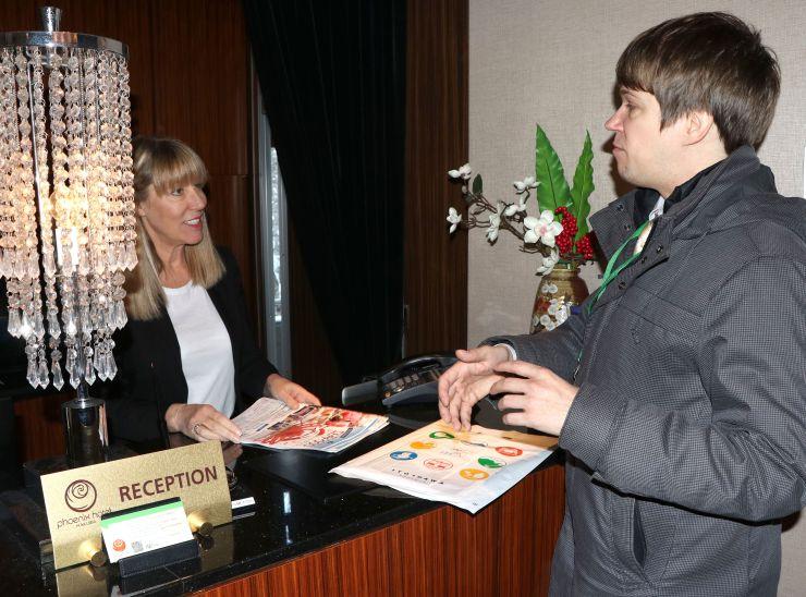 糸魚川の海の幸などをホテルのスタッフに説明する糸魚川市職員(右)=11日、長野県白馬村