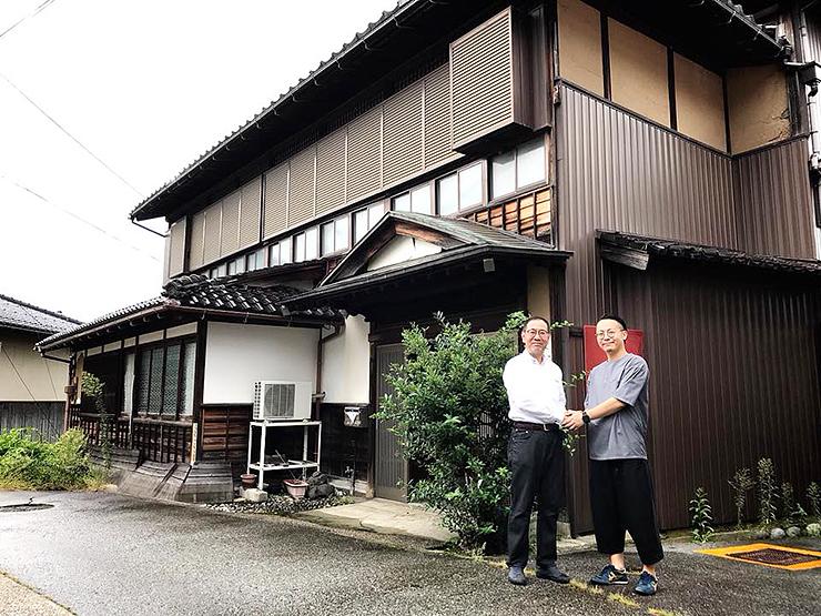 ゲストハウスに再生する古民家を背に握手する東会長(左)と山川代表=昨年9月、南砺市山見(コラレアルチザンジャパン提供)