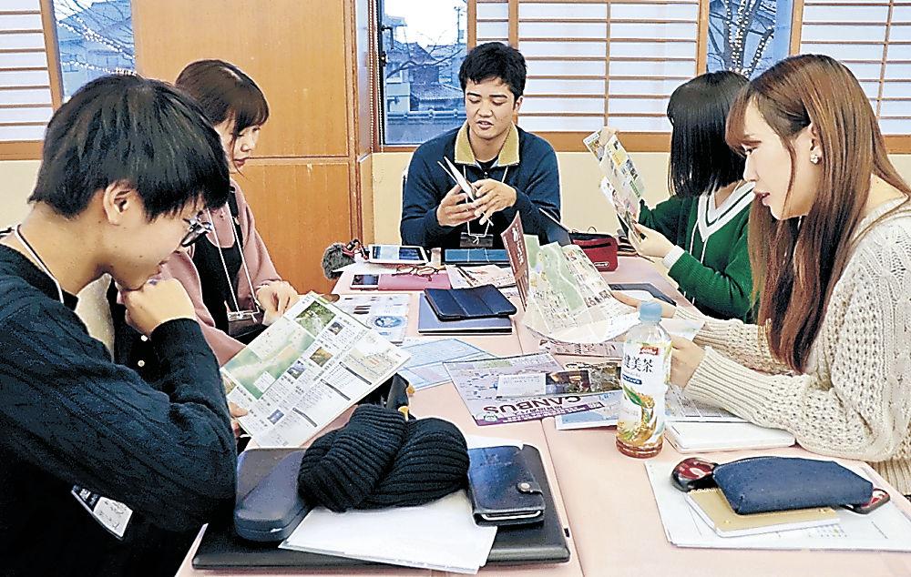 アプリ開発に向けて話し合う学生=加賀市内の旅館