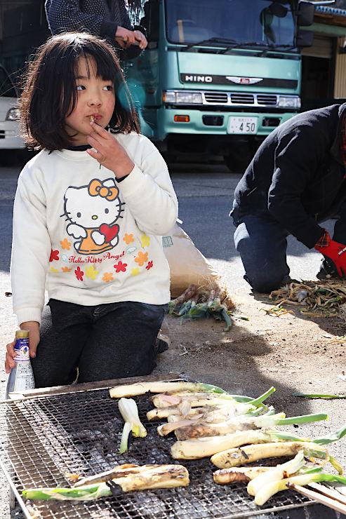 炭火で丸ごと焼いた千代ネギをおいしそうに頰張る子ども