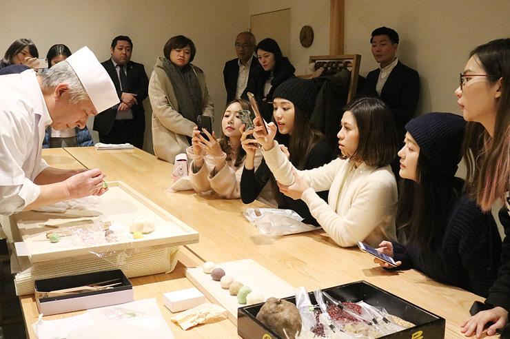 和菓子作りの様子を写真に収めるツアー参加者