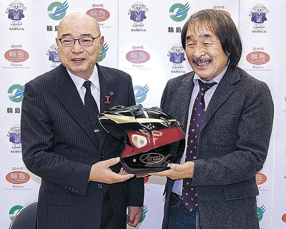 梶市長からヘルメットを受け取る風間さん(右)=東京・平河町の都道府県会館