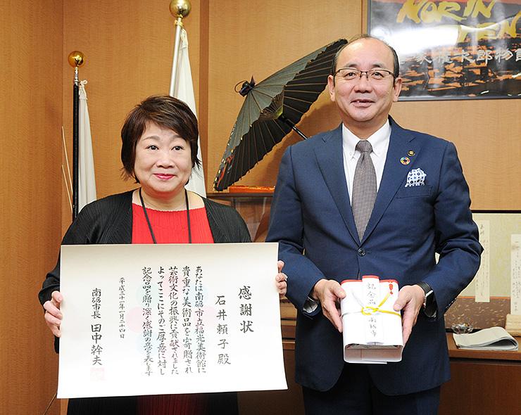 棟方の作品を市に寄贈し、感謝状を受けとった石井さん(左)=南砺市役所福野庁舎