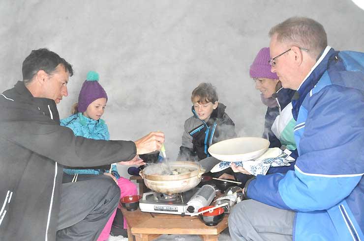 かまくらの中で鍋料理を味わうオーストラリアからのスキー客