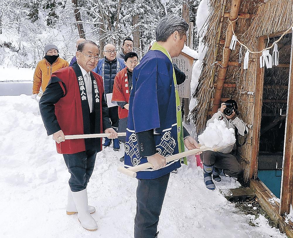 スコップを手に、氷室小屋に雪を詰める山城副会長(左)。今年は県人会メンバーが初参加した=湯涌温泉