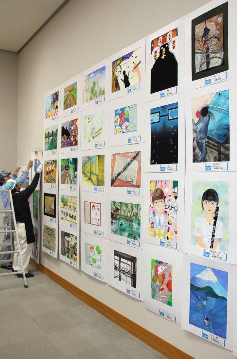個性豊かな作品が並ぶ県ジュニア美術展長岡展の展示作業=25日、長岡市中央図書館