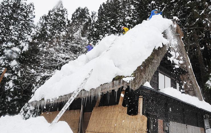 今冬で初となる屋根の雪下ろし作業に取り組む財団職員ら=相倉合掌造り集落