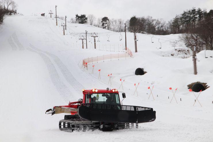 スキー場のオープンを前に圧雪車でゲレンデを整えるスタッフ=29日、上越市