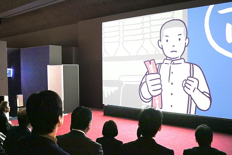 吉田忠雄さんの生涯と考え方を伝えるアニメーションに見入る関係者