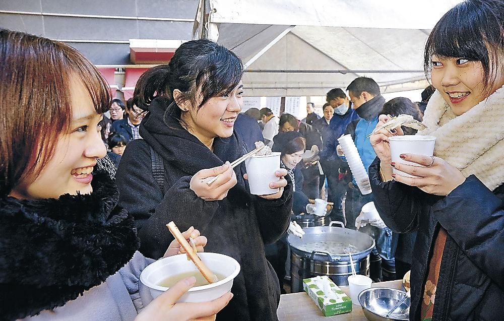 カニやブリが入った鍋を味わう観光客=近江町市場