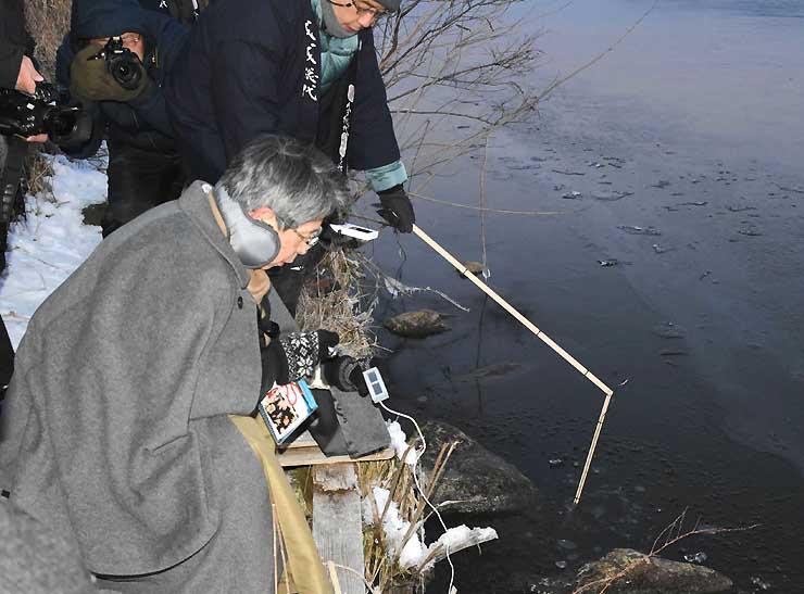 諏訪湖の水温を測る宮坂宮司(手前)