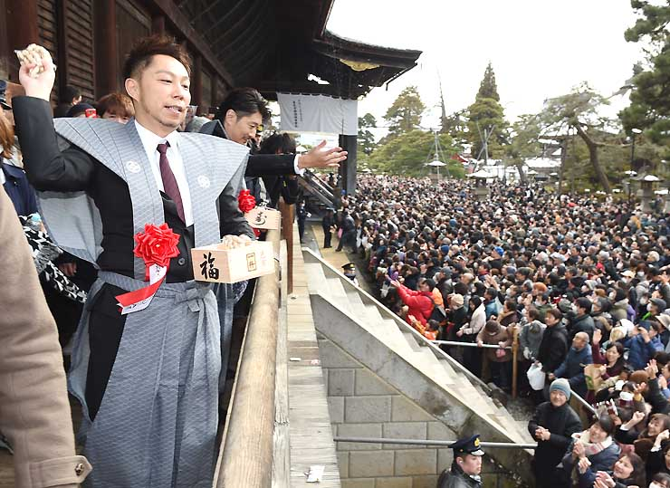 節分会で本堂周辺に集まった参拝者に豆をまく〓SAさん(手前左)。右隣がMAKIDAIさん=長野市の善光寺