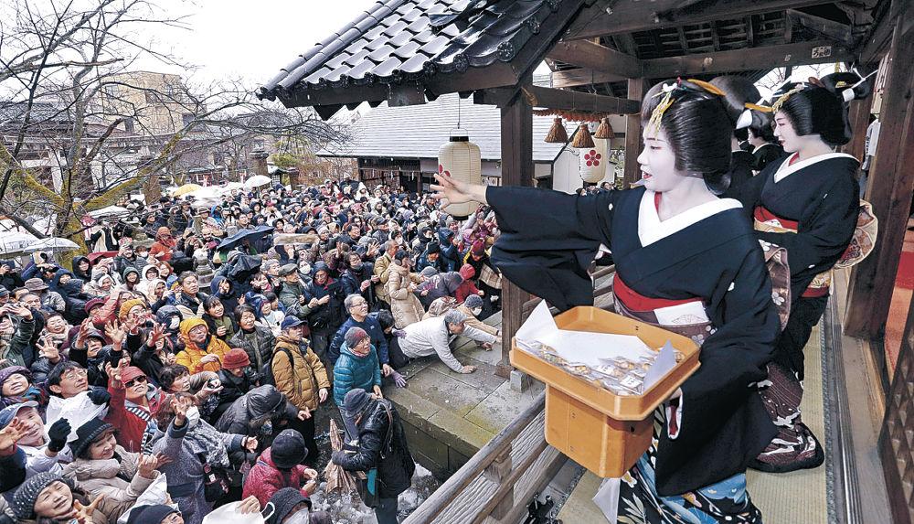 芸妓衆がまいた豆に手を伸ばす参拝客=金沢市東山1丁目の宇多須神社