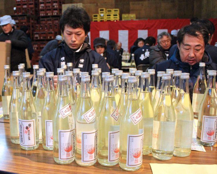 酒瓶に「立春朝搾り」のラベルを貼る作業=4日、柏崎市新橋の原酒造