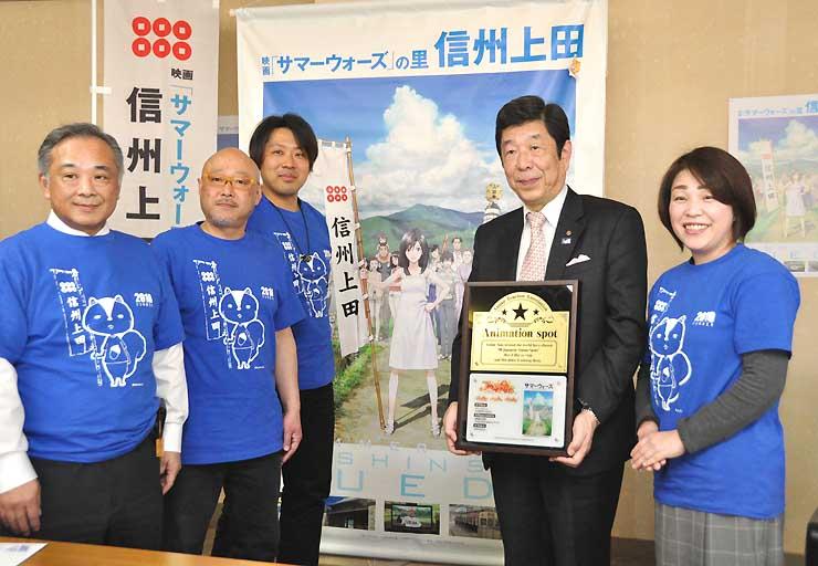 アニメの聖地の認定プレートを持つ柳沢理事長(右から2人目)と信州上田サマーウォーズ実行委員会のメンバーたち