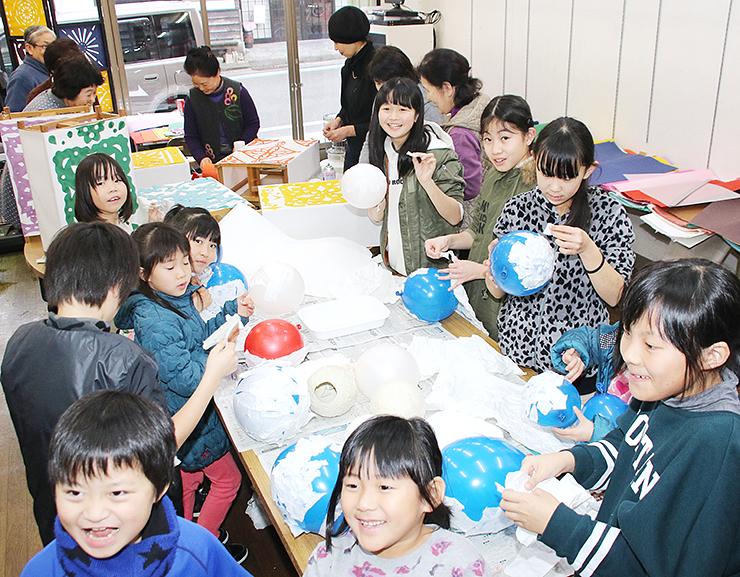 風船を型に和紙を貼って丸いあんどんを作る子どもたち