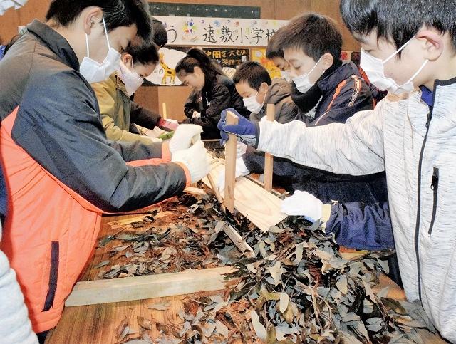 板からはみ出た葉を押し込みたいまつを完成させる児童=2月9日、福井県小浜市遠敷小