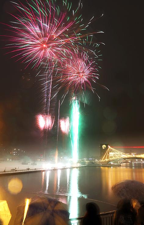 雪が降る中、夜空を彩った大輪の花火=富岩運河環水公園