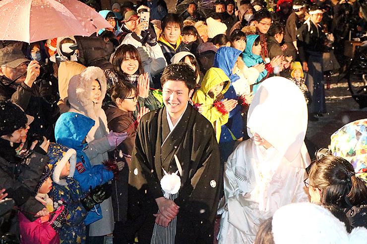 大勢の来場者に祝福されながら、ステージへ向かう中山さん夫婦(手前中央)