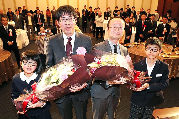 山田竜輝君(左)と油本綾花さん(右)から花束を贈られ、笑顔を見せる渡辺棋王(中央左)と挑戦者の広瀬竜王(同右)=魚津市のホテルグランミラージュ