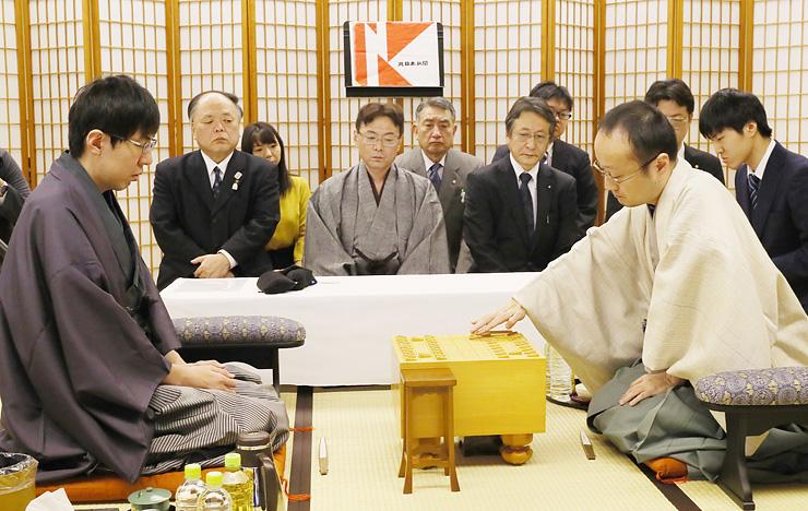 先手で駒を進める渡辺棋王(右)と、挑戦者の広瀬竜王。立会人の塚田九段(中央)らが見守った=新川文化ホール